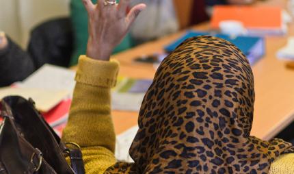 Muslim woman with hand raised