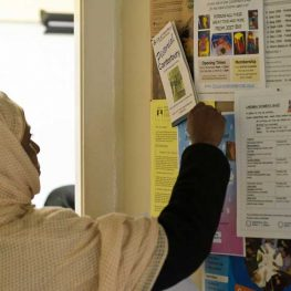 Muslim woman at noticeboard